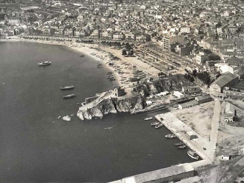 Vista aèria del passeig i la platja amb la punta dels Guíxols en primer terme, 1965 AMSFG. Col·lecció Municipal d'Imatges (Autor: Paisajes Españoles Fotografías Aéreas)