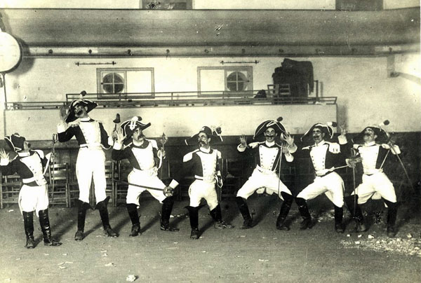 """Retrat de la colla de Carnaval dels """"Nyinyus"""" formada pel """"Nyinyo"""", en Felip, en Salmeron, el Gruixut, en Cosme, en Manau i en Clarel, caracteritzats com a carabinieri per representar el número dels calabresos en el segon ball de la temporada carnavalesca de l'any 1921 al Teatre Vidal. AMSFG. Col·lecció Santiago Güitó (Autor: Desconegut)"""