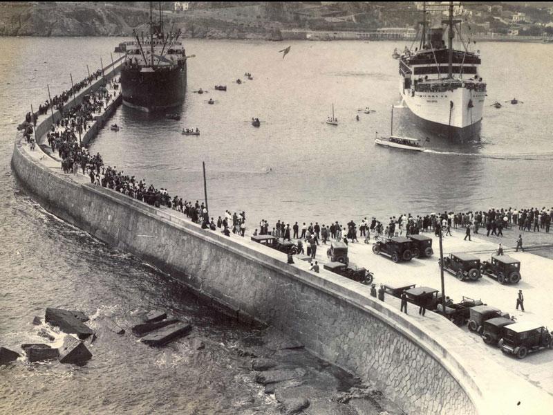El port comercial de Sant Feliu ple de gent esperant l'arribada d'un vaixell de passatgers (1925 – 1935). AMSFG. Fons Espuña – Ibañez. Autor: Desconegut.