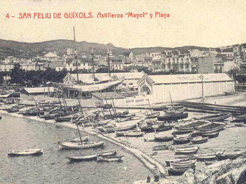 Les drassanes Mallol al racó de Llevant de la platja de Sant Feliu amb el veler Sant Jordi en construcció (1918 – 1921). AMSFG. Fons Ajuntament de Sant Feliu de Guíxols. Autor: Desconegut.