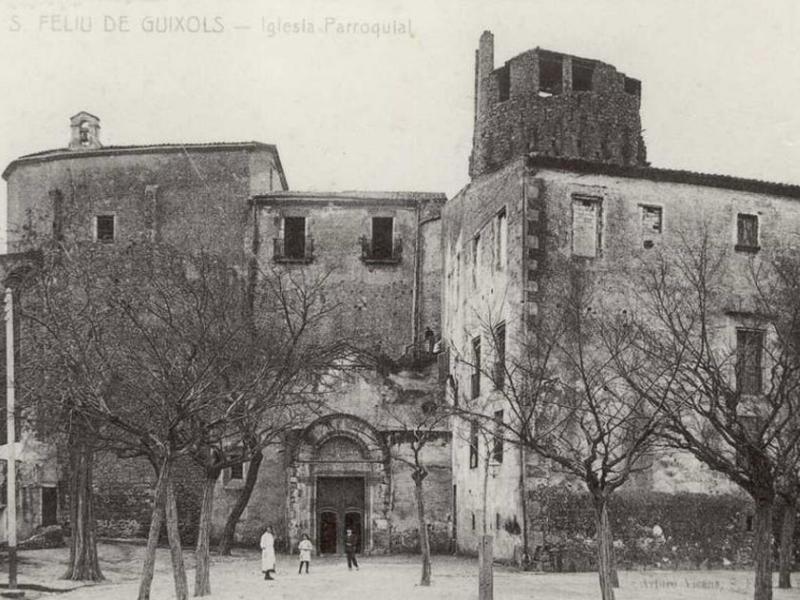 Vista de la plaça del Monestir i l'església parroquial de Nostra Senyora dels Àngels de Sant Feliu de Guíxols a principis del segle XX. AMSFG. Col·lecció Municipal d'Imatges (Autor desconegut).