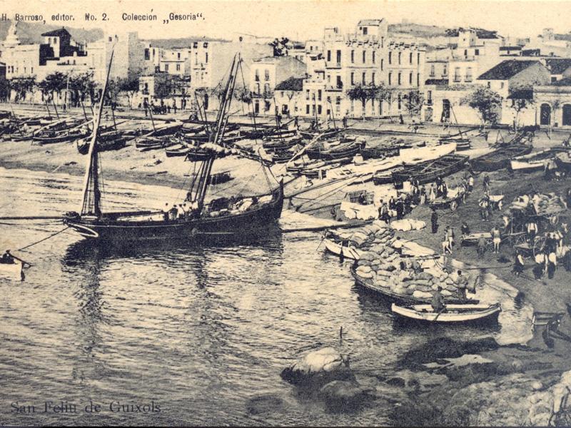 AMSFG. Fons Ajuntament de Sant Feliu de Guíxols. Autor: Desconegut. El racó de Llevant ple de treballadors realitzant feines de càrrega i descàrrega de mercaderies d'una barca de mitjana (1899 – 1905).