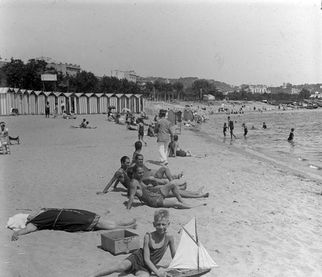 Casetes de banys al racó de garbí amb diversos banyistes a la sorra (1922 – 1930). AMSFG. Fons Francesc Llorens. Autor: Francesc Llorens.