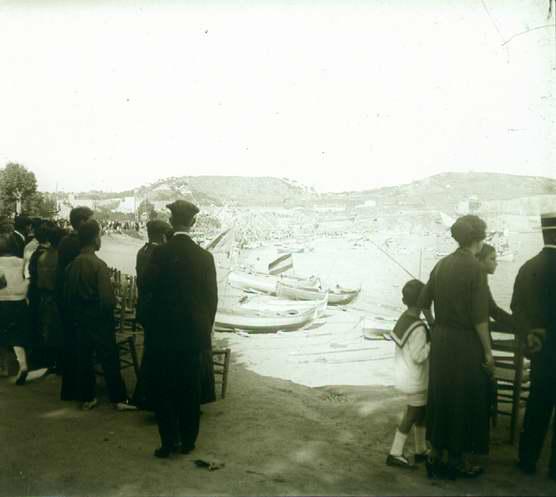 Platja de Sant Feliu de Guíxols plena de gent observant com salpen les barques engalanades AMSFG. Fons Francesc Llorens (Autor: Francesc Llorens)