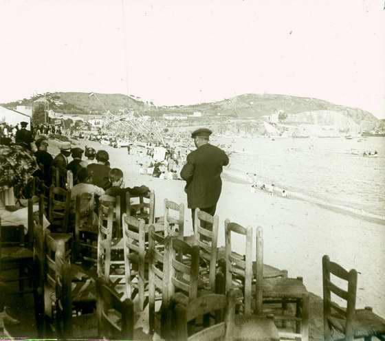 Platja de Sant Feliu de Guíxols amb ambient de festa i els llaguts adornats amb banderes espanyoles, 1919. AMSFG. Fons Francesc Llorens (Autor: Francesc Llorens)