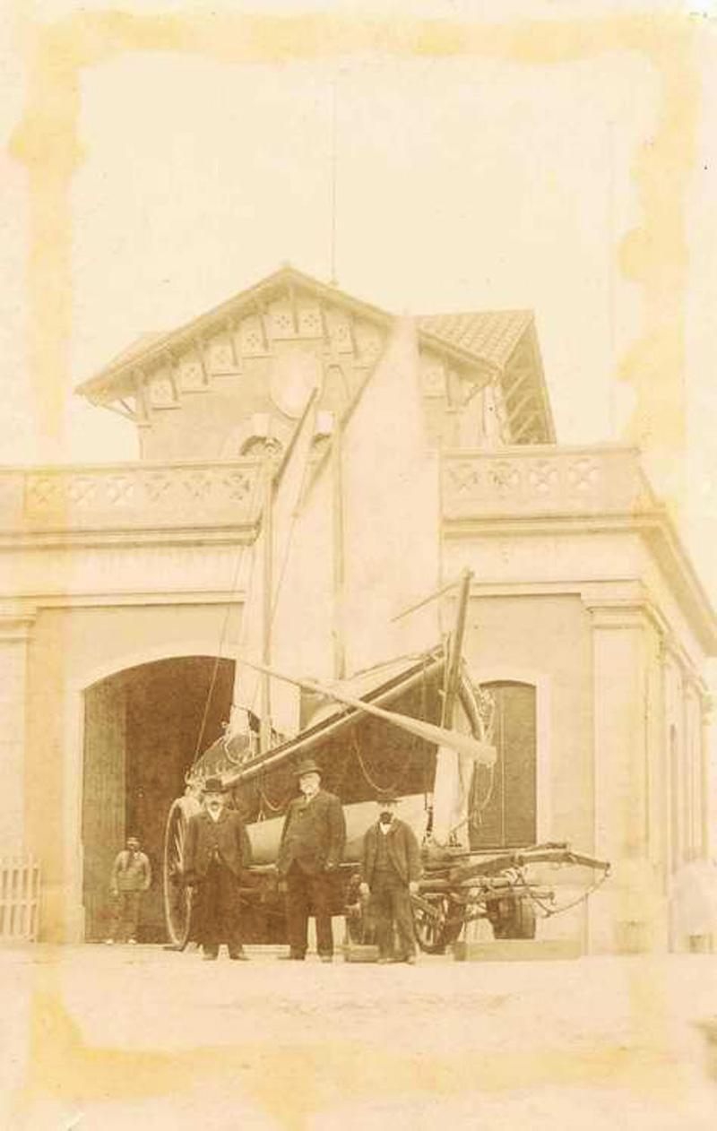 Retrat d'un grup davant del bot i la caseta de Salvament de Nàufrags al final del segle XIX. AMSFG. Col·lecció Espuña-Ibáñez. (Autor desconegut).