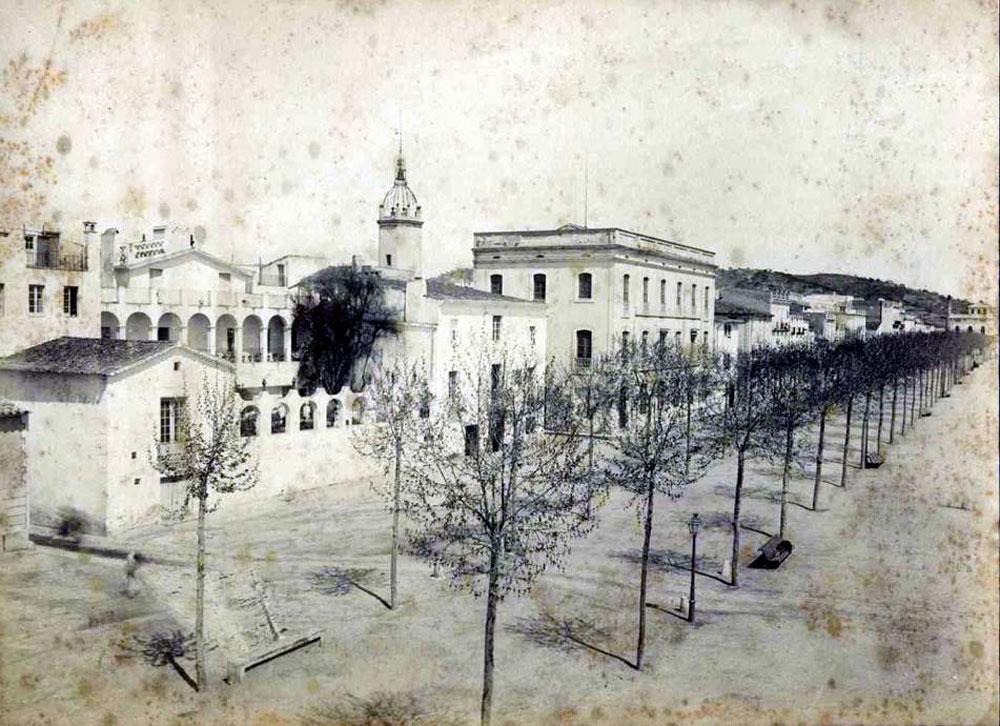 Passeig amb l'edifici de l'escola pública adjunt a l'Ajuntament, entre 1882 i 1889 AMSFG. Col·lecció Espuña-Ibáñez (Autor: Jaume Bertran)