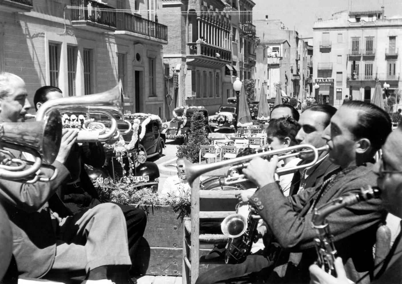 Orquestra tocant a la rambla del Portalet durant la desfilada de Sant Cristòfol, als anys 40. AMSFG. Fons Pere Rigau (autor Pere Rigau)