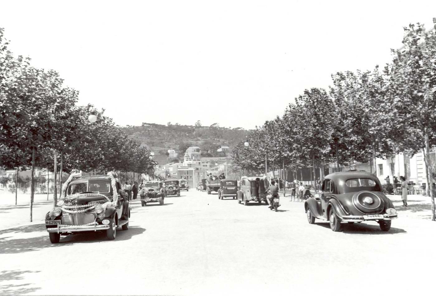 Cotxes engalanats per a la benedicció de la diada de Sant Cristòfol al passeig del Mar, anys 40 AMSFG. Fons Pere Rigau (autor Pere Rigau)