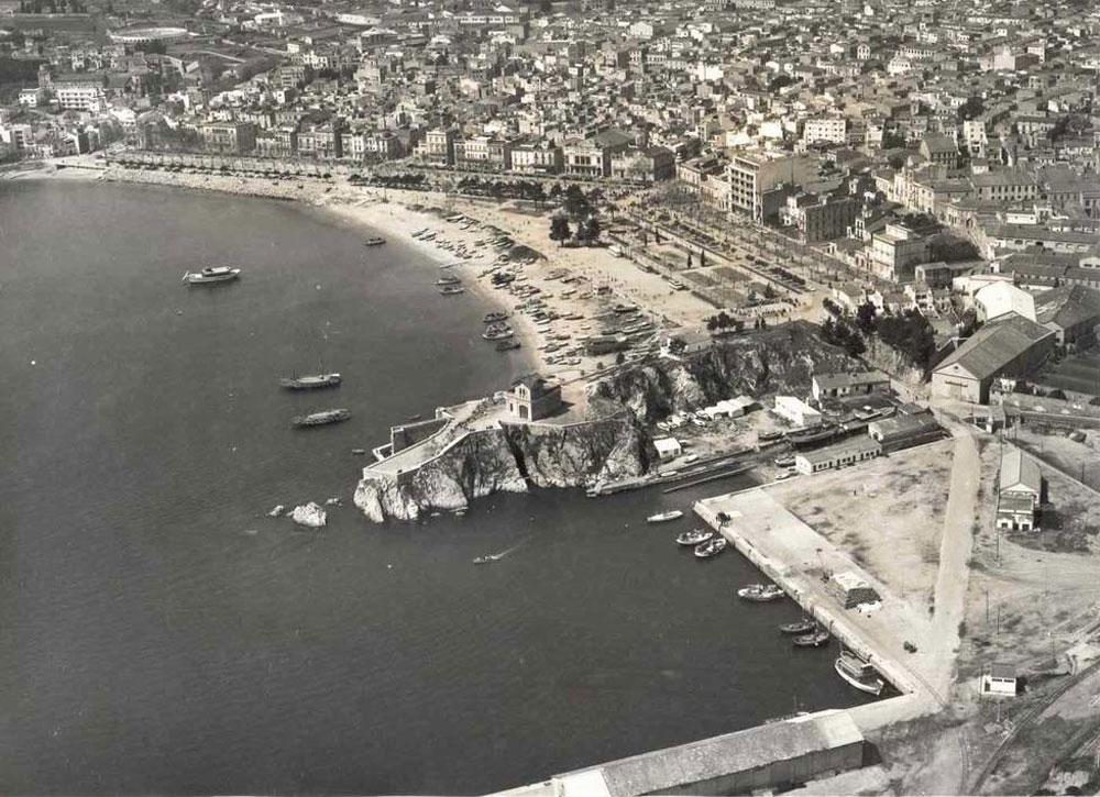 Vista aèria del passeig i la platja amb la punta dels Guíxols en primer terme, 1965 AMSFG. Col·lecció Municipal d'Imatges (Autor: Paisajes Españoles Fotografías Aéreas).