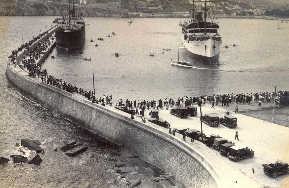 El port de Sant Feliu ple de gent esperant l'arribada d'un vaixell de passatgers (1925 – 1935). AMSFG. Fons Espuña – Ibañez. Autor: Desconegut.